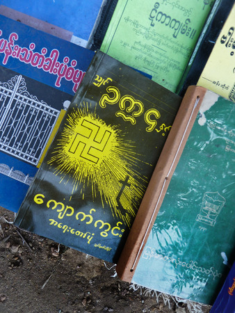 Close up of a used book on a street bookseller's table in Yangon, Burma. The book features an Asian Swaztika, an ancient and holy Buddhist and Hindu symbol which was famously adopted and misused by Nazi Germany.