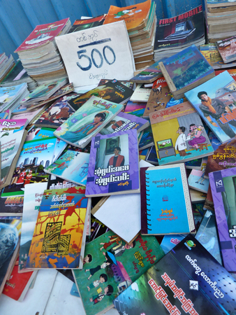 Closer View of used and second hand books on a sidewalk booksellers table in Yangon, Myanmar.  Books appear to be priced at 500 Kyat apiece, or about 60 US cents. Titles range from English to Myanmar and beyond, in varying conditions.