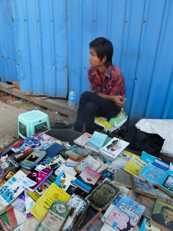 literary: View of a youthful sidewalk bookseller at his table in Yangon, Myanmar where he sells used and second hand books along the roadside. The literary community in Myanmar is surprisingly robust considering the country had been closed for decades. Editorial