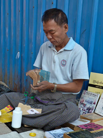 neighboring: A street bookseller in Yangon, Myanmar Burma repairs a paperback while minding his display. Unlike neighboring ASEAN countries, Myanmar has a thriving street bookseller community.