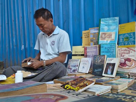 neighboring: Medium close up of a street bookseller in Yangon, Myanmar Burma repairs a paperback while minding his display. Unlike neighboring asian countries, Myanmar has a thriving street bookseller community. Editorial