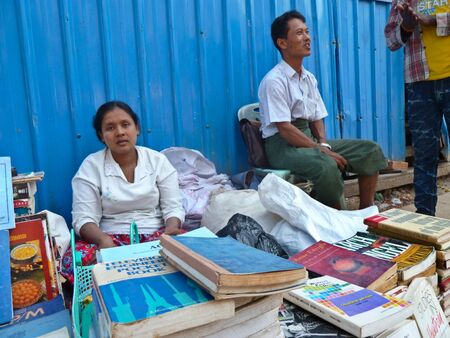 neighboring: A female and male street bookseller seen sitting behind a table of used and second hand novels, paperbacks and books. Unlike neighboring asian countries, Myanmar has a thriving street bookseller community. Editorial