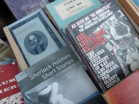 Close up view of used books on a street booksellers table in Burma. Note a book by Shakespeare on the left with a hand sewn binding. Editorial