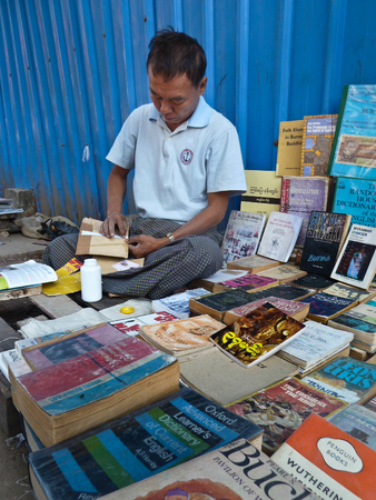 literary: View of a sidewalk bookseller repairing a book at his table in Yangon, Myanmar where he sells used and second hand books along the roadside. The literary community in Myanmar is surprisingly robust considering the country had been closed for decades.