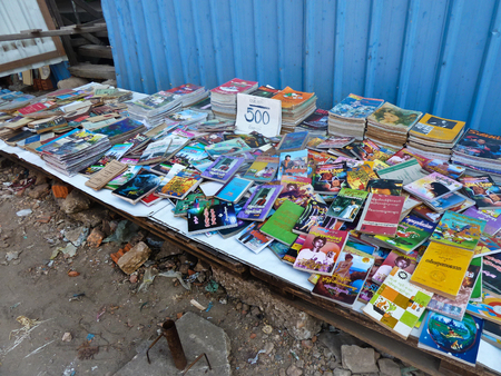 priced: Medium View of used and second hand books on a sidewalk booksellers table in Yangon, Myanmar.  Books appear to be priced at 500 Kyat apiece, or about 60 US cents. Titles range from English to Myanmar and beyond, in varying conditions.