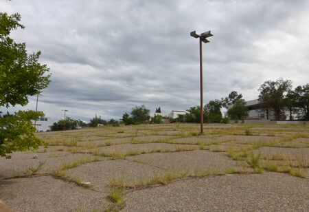 urban decline: An abandoned derelict parking lot at an industrial location with grass growing through cracks. No vehicles are visible, with cloudy skies above. Stock Photo