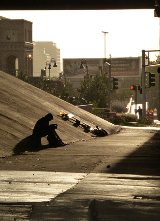 hardship: Shadow of a person sitting under an American highway overpass, seeking shelter from the elements. The individual could be a drug addict, alcoholic, or simply a person stopping to rest.