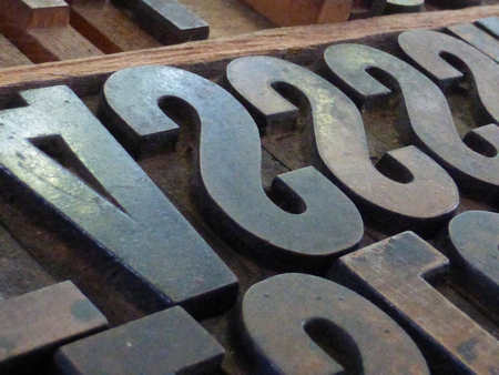 printing press: Horizontal Macro Close up of large metal moveable type block letters, used in printing presses prior to the digital age. Trays of type were pressed against a page to create text.