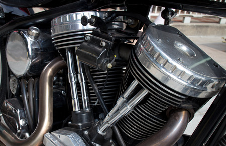 gleaming: Gleaming chrome cylinder head of vintage motorcycle engine. Other components, including part of tailpipe and gearbox, are also visible Stock Photo