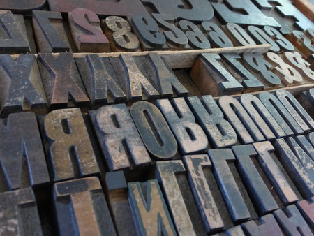 medium close up: Medium Close up of large metal moveable type block letters, used in printing presses prior to the digital age. Trays of type were pressed against a page to create text.