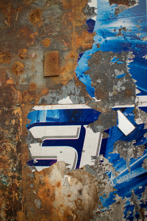 old items: Vertical view of Rusty weathered metal wall indiscernable blue remnant of old poster or flyer on it Paper and other items have partially flaked off, producing interesting textures with deep metal rust color.
