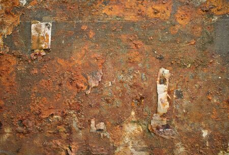 old items: Horizontal view of Rusty weathered metal wall with bits of Paper and debris hanging off it. Old thumbtack visible on frame. Paper and other items have partially flaked off, producing interesting textures with deep metal rust color.