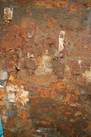 flaked: Vertical view of Rusty weathered metal wall with bits of Paper and debris hanging off it. Paper and other items have partially flaked off, producing interesting textures with deep metal rust color.