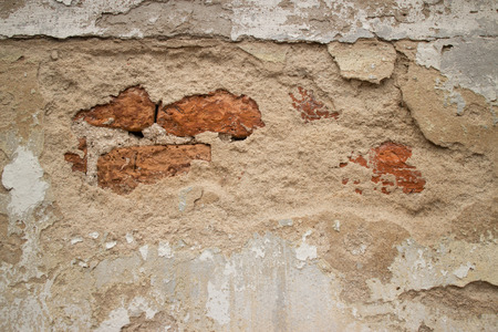 stucco texture: View of a Broken Stucco Colonial Stucco Wall in Asia with Slight Brick showing through the beige foundation.