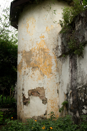 shipped: Medium shot of old corner guard tower at colonial era prison in Southeast Asia. White curved stucco surface is shipped and faded, with vegetation below and above.