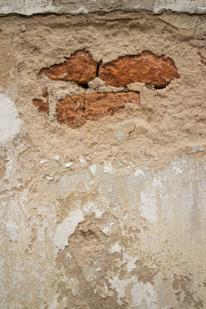 broken through: View of a Broken Stucco Colonial Stucco Wall in Asia with Slight Brick showing through the beige foundation - vertical orientation.
