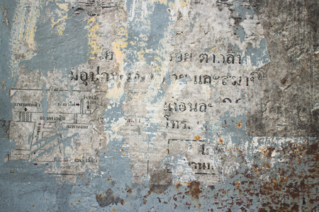 scraped: Abstract Texture on a wall in Thailand. Remnants of scraped off paper include faint, indiscernable Thai lettering next to a rust colored background.