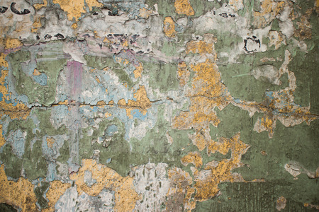 fissures: Old cracked wall in Thailand with flecks of paper and chipped green and beige paint remnants. Cracks and fissures span this eroded surface. Stock Photo