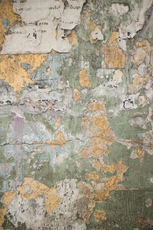 flecks: Old cracked wall in Thailand with flecks of paper and chipped green and beige paint remnants. The primary. Cracks and fissures span this eroded surface. Stock Photo