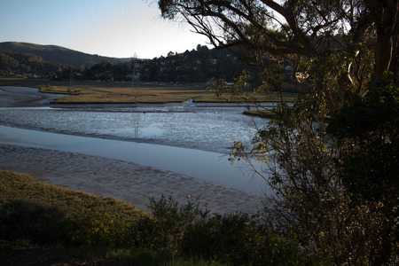 Closer view of shallow tide on a residential ocean inlet in Northern California, USA. Located in Marin county, this public space reveals the natural tidal patterns of a developing area.