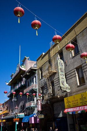 plurality: Vertical view of Red Chinese Lanterns hanging across a street in San Franciscos Chinatown. Many of the buildings in this area were built in the early 1900s.