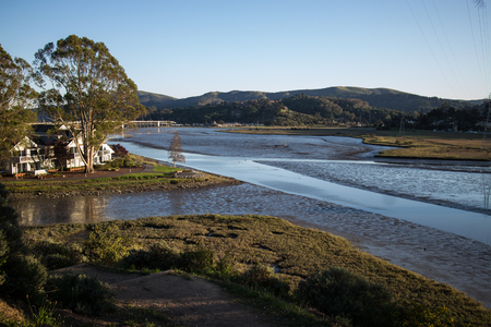 marin: Shallow tide on a residential ocean inlet in Northern California, USA. Located in Marin county, this public space reveals the natural tidal patterns of a developing area. Stock Photo
