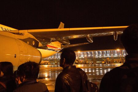 redeye: Passengers walk across the tarmac to board a connecting flight at Beijing International airport. The rainy runway surface at night reveals the time and weather.