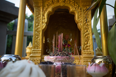 burnt out: Detail of a residental spirit house shrine in Southeast Asia, with burnt out incense sticks visible. A pork bun can be seen on the lower left; offerings are made to deceased relatives and local spirits alike.