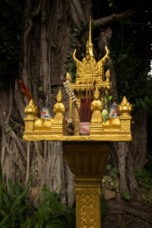 deceased: Mediumclose up of a gold spirit house with large tree shimmering in the dusky afternoon in Southeast Asia. At the spirit house, offerings are made to local spirits and deceased relatives.