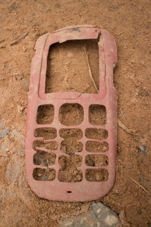 antiquated: Ground level closeup view of a dusty, broken older style mobile phone face lying in the dust at the side of the road. Changes in technology can drive products into and out of business at an extreme pace.