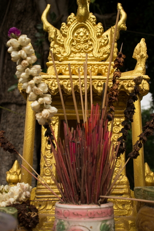 deceased: Extreme close up detail of a gold spirit house in Southeast Asia, with incense and flowers at center vertical. At the spirit house, offerings are made to local spirits and deceased relatives.