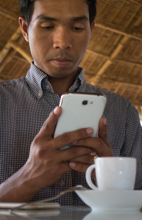 medium close up: Low angle vertical medium close up shot of male person of color looking at his smartphone Phablet in a rustic beach cafe-like environment. A coffee cup and second smart phone are visible on the table. Stock Photo