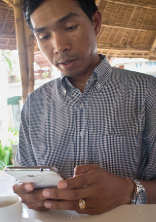 medium shot: Low angle vertical medium shot of male person of color looking at his smartphone Phablet in a rustic beach cafe-like environment. Exterior and interior elements can both be seen.