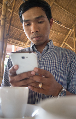 medium shot: Low angle vertical medium shot of male person of color looking at his smartphone Phablet in a rustic beach cafe-like environment. Coffee cups can be seen in the foreground of this cafe-like environment. Stock Photo