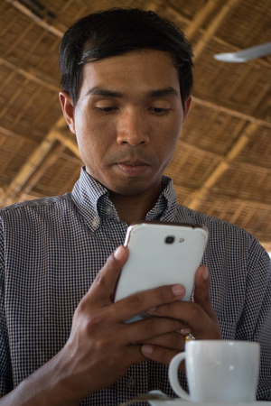 medium close up: Low angle vertical medium close up shot of male person of color looking at his smartphone Phablet in a rustic beach cafe-like environment. A coffee cup is partly visible in the foreground. Stock Photo