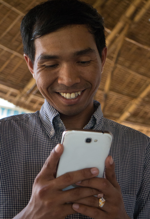 medium close up: Low angle vertical medium close up shot of smiling male person of color looking at his smartphone Phablet in a rustic beach cafe-like environment. Stock Photo