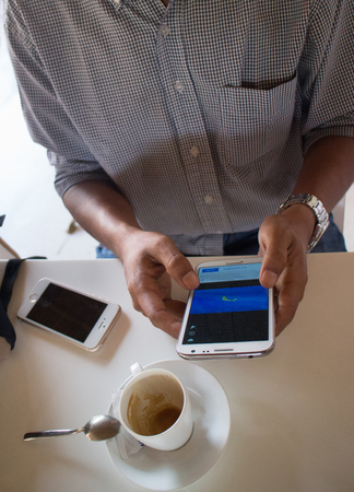 medium shot: High angle medium shot of a male person of color looking at a smartphone Phablet in a cafe-like environment. A coffee cup and another smartphone can be seen nearby.