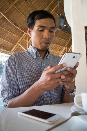 medium shot: Low angle vertical medium shot of male person of color looking at his smartphone Phablet in a rustic beach cafe-like environment. Another smartphone is visible in foreground, with coffee cup nearby.