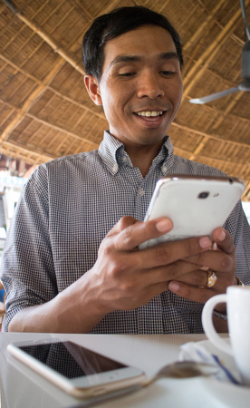 medium shot: Low angle vertical medium shot of smiling male person of color looking at his smartphone Phablet in a rustic beach cafe-like environment. A second smartphone and partial coffee cup can be seen nearby
