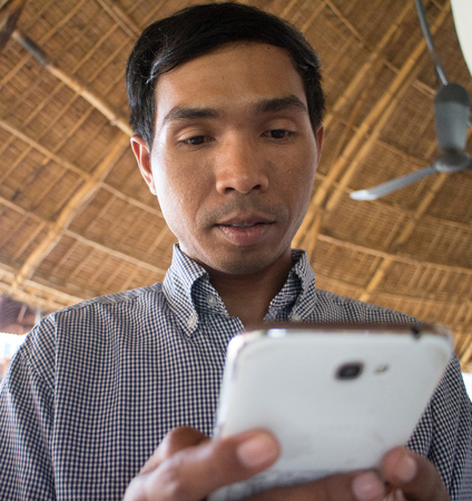 medium shot: Low angle medium shot of male person of color looking at his smartphone Phablet in a rustic beach cafe-like environment. A second smartphone and partial coffee cup can be seen nearby