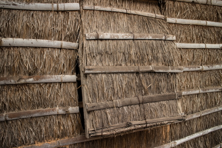 Medium shot of grass thatched house wall and window-flap in Cambodia, Asia. The cross bars supports are made from strips of bamboo.