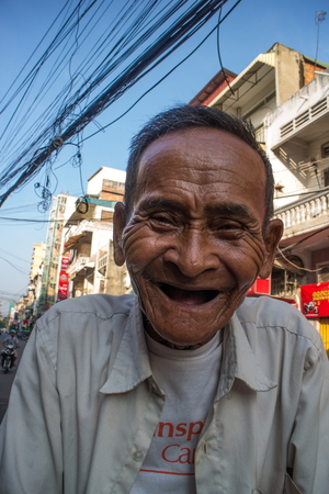 medium shot: Vertical medium shot of 87 year old bicycle cab (cyclo) driver in Southeast Asia. Local buildings and overhead lines are visible with a blue sky above.
