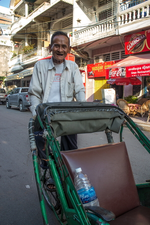 medium shot: Vertical medium shot of 87 year old bicycle cab (cyclo) driver in Southeast Asia, with his cyclo visible. Local buildings and overhead lines are visible with a blue sky above.