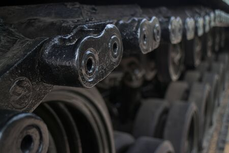 Extreme close up detail of tread assembly links on captured US Army tank on display in Ho Chi Minh City, Vietnam. Wheel assemblies can be seen indistinctly below.