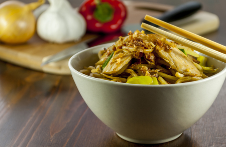 chinese noodle with chicken and vegetables on wood table photo