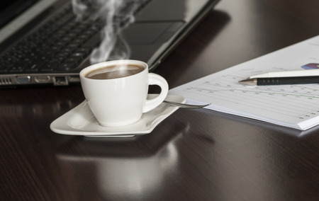Open black laptop and hot cup of coffee on wood table photo