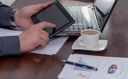 Man works in bussiness office with computer or laptop or notebook and papper graf and he drinks coffee photo