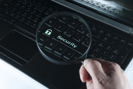 mans hand with magnifying glass above computer keyboard with notice security photo