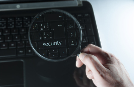 mans hand with magnifying glass above computer keyboard photo