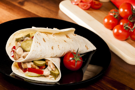 Tortilla with tomato and chicken meat and cucumber on black plate photo